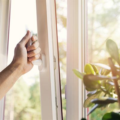 domestic ventilation - hand open white plastic pvc window at home